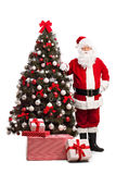 Santa Claus standing next to a Christmas tree. Full length portrait of Santa Claus standing next to a Christmas tree and looking at the camera isolated on white Stock Image
