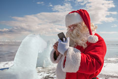 Santa Claus standing outdoors at ice. Santa Claus that calls to whom by phone royalty free stock photos
