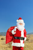 Santa Claus standing outside, with presents Stock Image