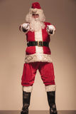 Santa Claus standing and pointing at the camera. On studio background Stock Photo