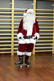 Santa Claus standing on skateboard in fitness studio Royalty Free Stock Image