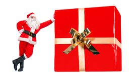 Santa Claus stands by the large Christmas gift royalty free stock images