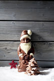 Santa claus star shaped christmas decoration chocolate christmas tree on heap of snow against wooden background Stock Photos
