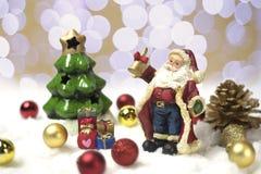 Santa Claus steht auf Schnee mit seiner Handglocke Stockbild