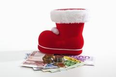 Santa Claus-Stiefel- und -Euromünzen auf aufgelockerten Euroanmerkungen gegen weißen Hintergrund Lizenzfreie Stockfotos