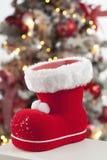 Santa Claus-Stiefelabschluß herauf Weihnachtsbaum im Hintergrund Stockfotografie