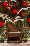 Santa Claus stol under den dekorerade julgranen Royaltyfri Foto