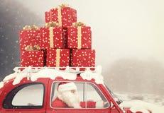 Santa Claus su un'automobile rossa in pieno di regalo di Natale Fotografia Stock Libera da Diritti