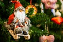 Santa Claus su un giocattolo della slitta sull'albero di Natale Fotografia Stock