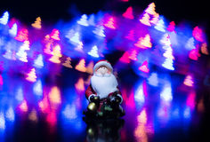 Santa Claus sui precedenti di bokeh variopinto sotto forma di alberi di Natale Fotografie Stock