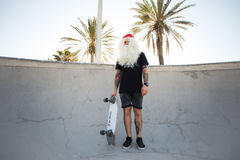Santa Claus on summer vacation. Hipster millennial man dressed up as santa claus with whote beard and hair, has tattoos on arms, poses with skateboard inside stock image