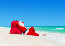 Santa Claus sunbathe on Christmas gifts sack at ocean beach Royalty Free Stock Photography