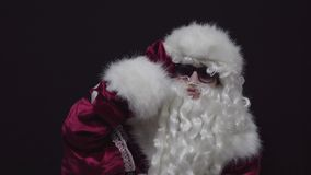 Santa Claus in Sunglasses Looking Away and Seeking Good Children against black background. stock footage