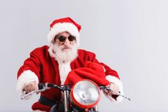 Santa Claus In The Sunglasses Riding A la motocicleta y sostener su bolso imagen de archivo