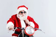 Santa Claus In The Sunglasses Riding A The Motorcycle And Holding His Bag. Santa Claus with a white beard wearing sunglasses and Santa outfit riding a motorcycle royalty free stock photos