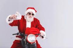 Santa Claus In The Sunglasses Sitting en la motocicleta y el dinero el sostenerse foto de archivo libre de regalías