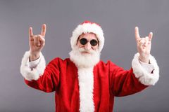 Santa Claus In The Sunglasses Standing And Showing A Rock Gesture. Portrait of Santa Claus with a white beard wearing sunglasses and Santa outfit standing and stock photos