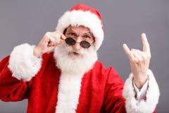 Santa Claus In The Sunglasses Standing y mostrar un gesto de la roca imágenes de archivo libres de regalías