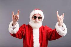 Santa Claus In The Sunglasses Standing y mostrar un gesto de la roca fotos de archivo