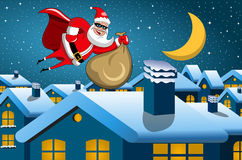 Santa Claus superhero flying nighttime town sack full xmas gifts Royalty Free Stock Images