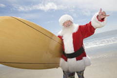 Santa Claus With Surf Board On-Strand Lizenzfreies Stockfoto