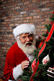 Santa Claus Surprised. Santa Claus looking surprised as he is sneaking around the Christmas Tree with copy space above him Royalty Free Stock Photography