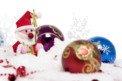 Santa claus surrounded by christmas balls on snow Royalty Free Stock Images