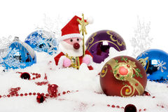 Santa claus surrounded by christmas balls on snow Stock Photo
