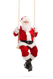 Santa Claus swinging on a wooden swing Stock Images
