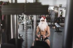 Santa Claus szkolenie w wioślarskiej maszynie po boże narodzenie wakacji Zdjęcie Stock