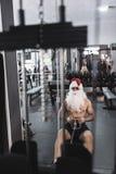 Santa Claus szkolenie w wioślarskiej maszynie po boże narodzenie wakacji Obraz Royalty Free