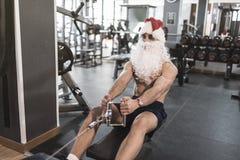 Santa Claus szkolenie w wioślarskiej maszynie po boże narodzenie wakacji Zdjęcia Royalty Free