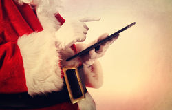 Santa Claus with tablet. Santa Claus using a digital tablet in vintage style Royalty Free Stock Photo