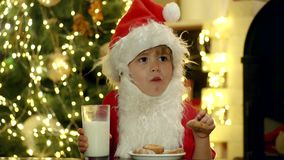 Santa Claus takes a cookie on Christmas Eve as a thank you gift for leaving presents. Greeting Christmas card. Portrait