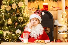 Santa Claus takes a cookie on Christmas Eve as a thank you gift for leaving presents. Portrait of surprised and funny