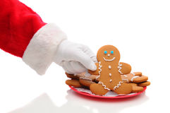 Santa Claus Taking Ginger Bread Man From Plate Royalty Free Stock Photography