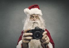Santa Claus taking holiday pictures royalty free stock images