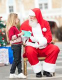Santa Claus Taking Letter From Girl lizenzfreies stockfoto