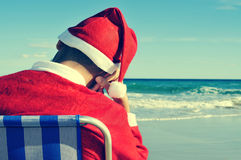 Santa claus taking a nap on the beach stock photos