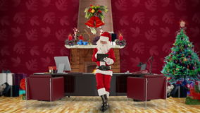Santa Claus taking notes on a clipboard in his modern Christmas Office, stock footage Royalty Free Stock Images