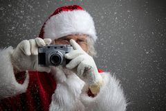 Santa Claus taking picture with old camera. Dark background with snow royalty free stock photo
