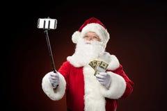 Santa Claus taking selfie. With dollars Royalty Free Stock Images