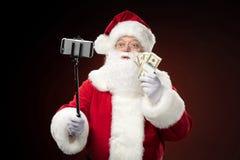 Santa Claus taking selfie. And showing dollars Royalty Free Stock Photo