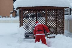 Santa claus taking with shovel snow away to make the way free in Stock Images