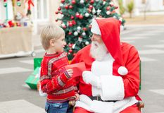 Santa Claus Taking Wish List From Boy Royalty Free Stock Photos