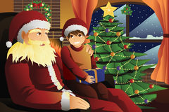Santa Claus talking with a kid on his lap Royalty Free Stock Photos