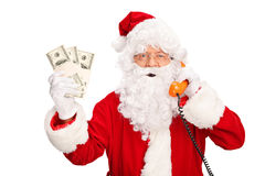 Santa Claus talking on phone and holding money Stock Photos