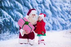 Santa Claus talking to little girl in snowy park Stock Images