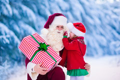 Santa Claus talking to little girl in snowy park Stock Image
