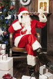Santa claus talking to smart phone. Sitting in armchair at his home stock images